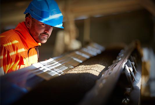 employé surveillant une chaine de fabrication d'un engrais
